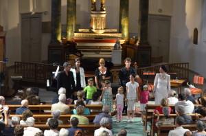 """Les musiciens entourant le choeur d'enfants, interprètes du conte musical """" La grande aventure """"."""